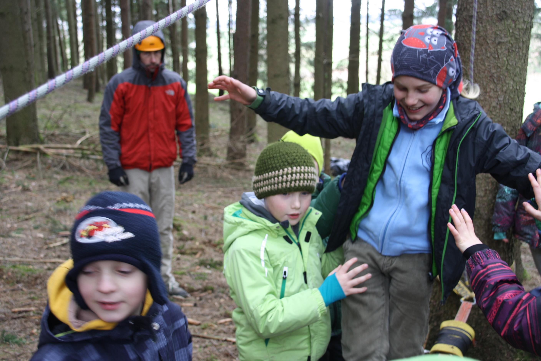 Kinder bewältigen gemeinsam einen Parcours auf Niedrigseilelementen